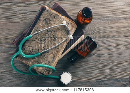 Books, pills and stethoscope on wooden table, top view