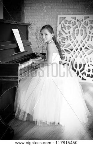 Beautiful girl playing on piano in classroom