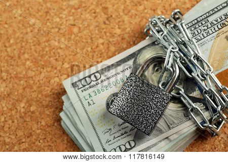 Dollars currency with lock and chain on wooden background