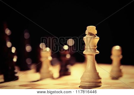 Chess pieces and game board on dark background