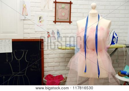 Tailor dummy with measuring tape in fashion studio