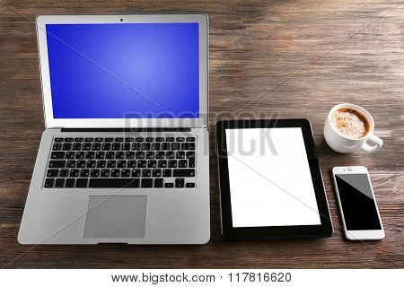 Modern laptop, mobile phone, tablet and coffee cup on wooden table