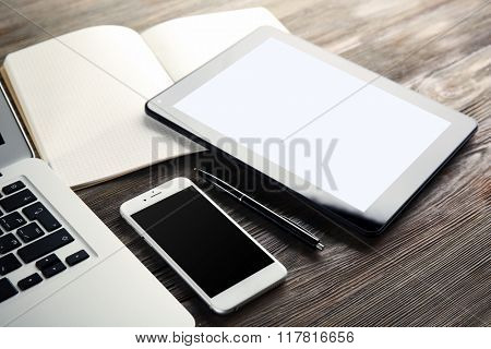 Modern laptop, tablet, mobile phone and notebook on the table, close-up