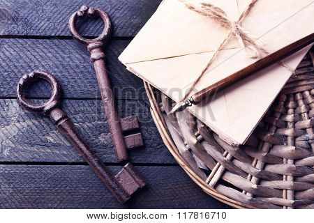 Old keys with papers, ink and pen on wicker mat against dark wooden background, close up