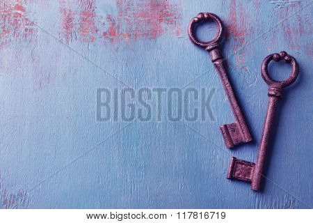 Old keys on blue wooden background, copy space