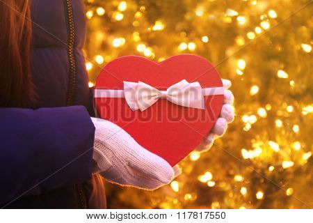 Red heart shaped box with bow in hands over lighted background