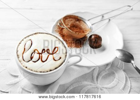 Cup of cappuccino with chocolate syrup and cacao powder on light wooden table