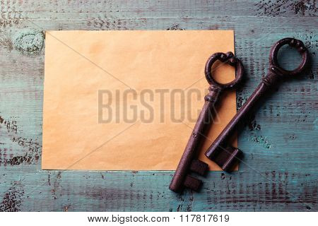 Old key with empty sheet of paper on blue wooden background, close up