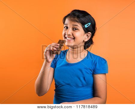 indian small girl with chocolate, asian small girl with chocolate, indian girl eating chocolate