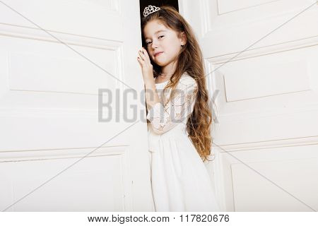 little cute girl at home, opening door well-dressed in white dress, adorable milk fairy teeth