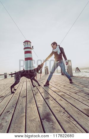 beautiful young woman playing with dog on the sea shore