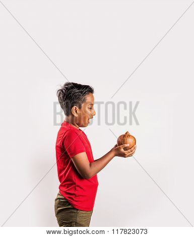 Handsome Indian kid looking surprisingly at piggy bank