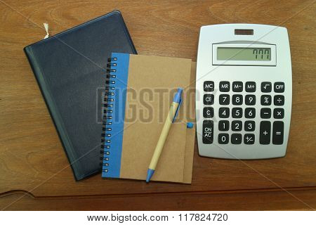 calendar,Notepad,pen and calculator on wooden background