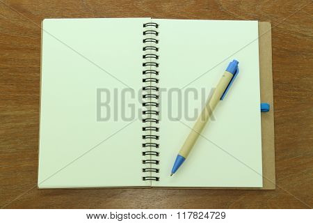 Open notepad and pen on wooden background
