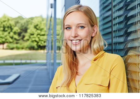 Young blonde businesswoman smiling next to her office outdoors