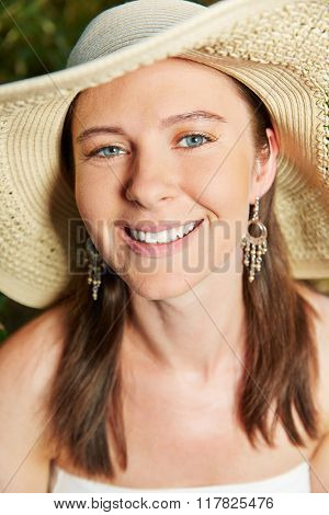 Smiling attractive woman with straw hat in summer