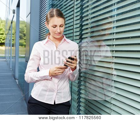 Businesswoman checking her smartphone display for news and messages