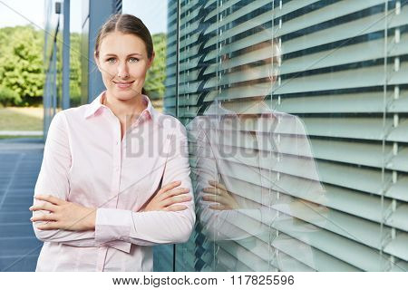 Young business woman standing next to the office with her arms crossed
