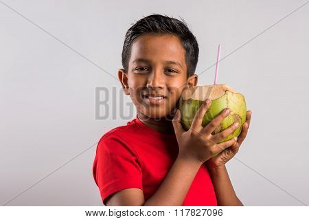 An handsome Indian kid drinking coconut water to cool off