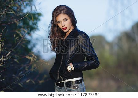 Young curious beautiful woman with bright trendy makeup wavy hairstyle in black leather jacket  and