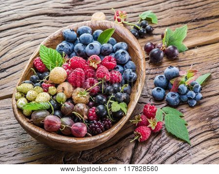 Ripe berries in the wooden bowl on the table.