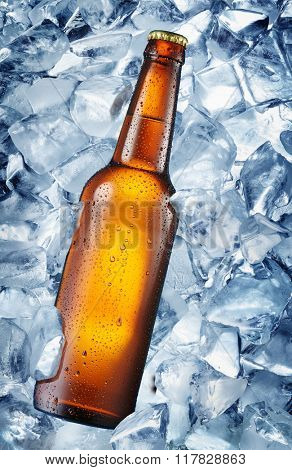 Cold bottle of beer in the ice cubes. There is condensated moisture over glass.
