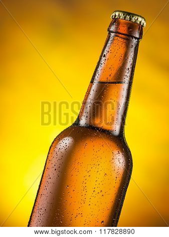 Cold bottle of beer with condensed moisture on it. Yellow background.