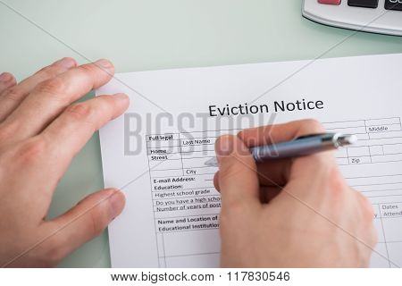 Person Hand Filling Eviction Notice Form