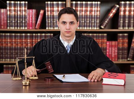 Portrait Of Young Judge Striking The Gavel At Table