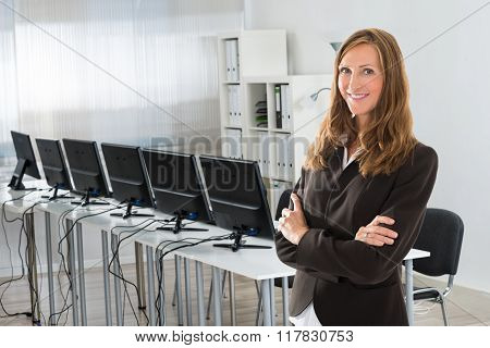 Female Manager Standing Arms Crossed In Office