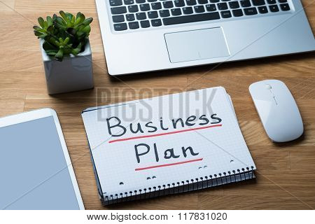 Business Plan Written On Notepad At Office Desk