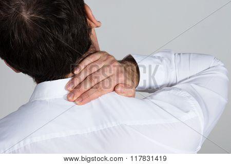 Rear View Of Businessman Suffering From Neckache
