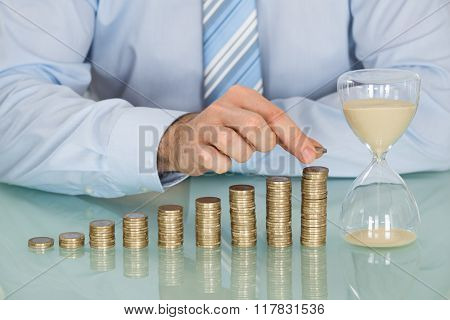 Businessman With Hourglass And Stack Of Coins