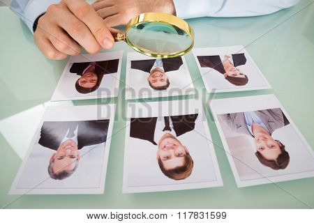 Person With Candidate Photograph And Magnifying Glass