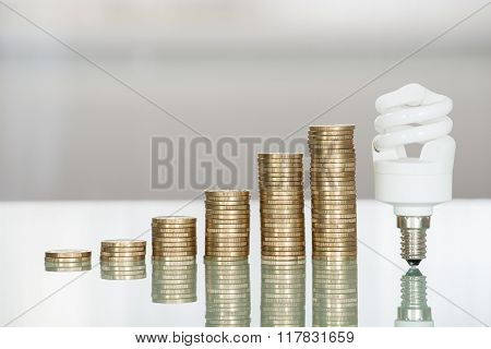 Fluorescent Light Bulb And Stacked Coins On Desk