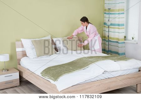Female Housekeeper Arranging Pillow On Bed