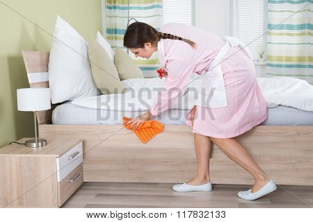 Female Housekeeper Cleaning Bed