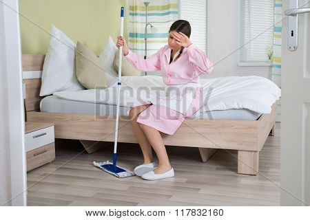 Tired Housekeeper Sitting On Bed With Mop