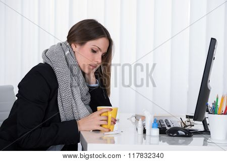 Businesswoman With Cup At Desk