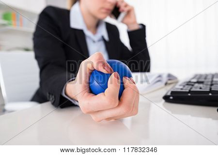 Businesswoman Pressing Stressball At Desk