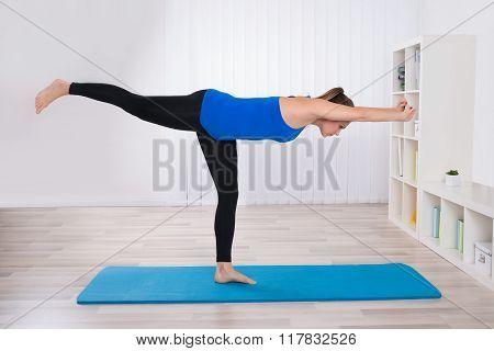 Female Doing Yoga In Her Living Room