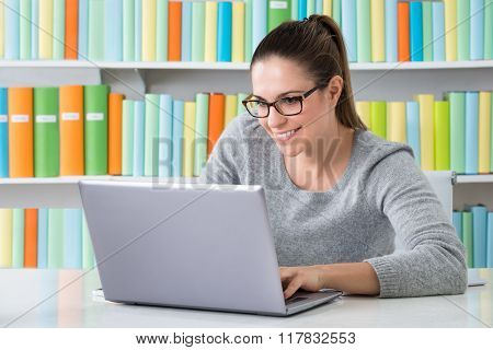 Woman Sitting In Library Using Laptop