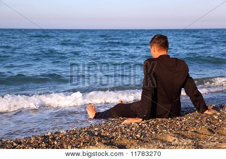 Barefooted Man In Business Suit Sits Back On Stone Coast At Evening
