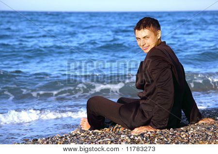 Barefooted Smiling Man In Suit Sits On Stone Coast At Evening
