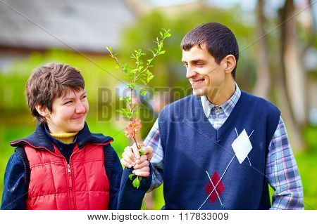 Portrait Of Happy Woman And Man With Disability Together On Spring Lawn
