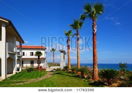 White Two-story House With Brown Roof, Green Lawn, Palm Trees On Coast