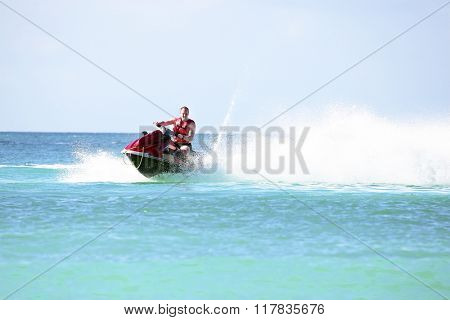 Young guy cruising on a jet ski on the caribbean sea