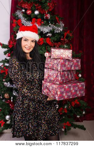 Happy Woman Holding Stack Of Christmas Gifts