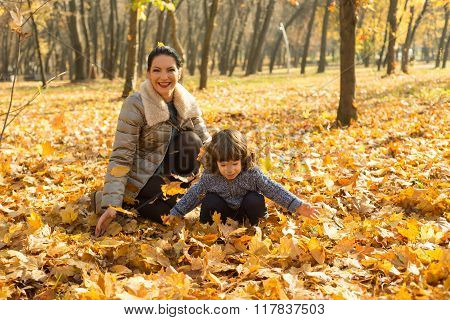 Happy Mom And Her Toddler Son In Autumn Park
