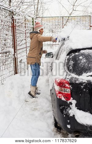 Woman Cleaning Snow Car